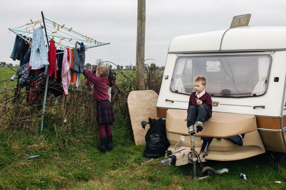 James is sitting on a campingbox while her sister is hanging up the clothers after coming back from school at the backroad, County Kildare, Ireland