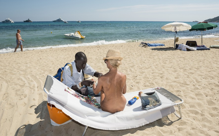 Title: Saint-Tropez, France From the series 'Mediterranean. The Continuity of Man' (2014) Caption: A Senegalese migrant sells a bracelet to a naked lady on a naturist strech of Pampelonne Beach in Saint Tropez.